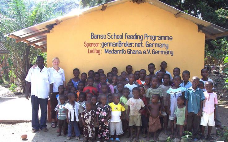Bettina Landgrafe zusammen mit Schülern vor einem durch Spenden finanzierten Schulgebäude in Ghana